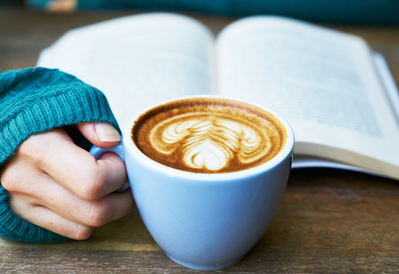reading a book while drinking coffee